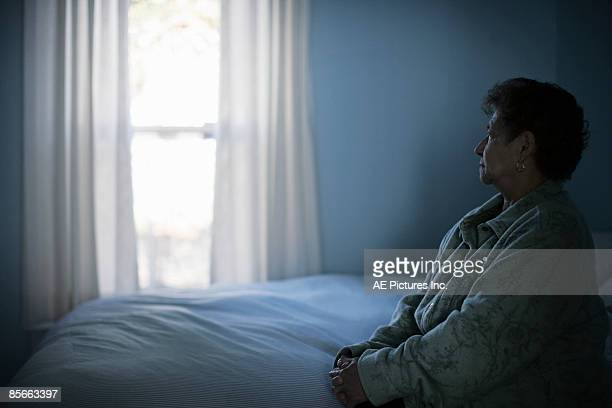 Mature woman sits on bed near window