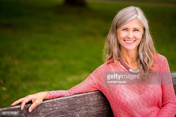 Mature Woman Sits On Park Bench