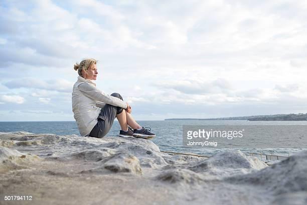 中年の女性一人で座って注ぎ、景色を眺める
