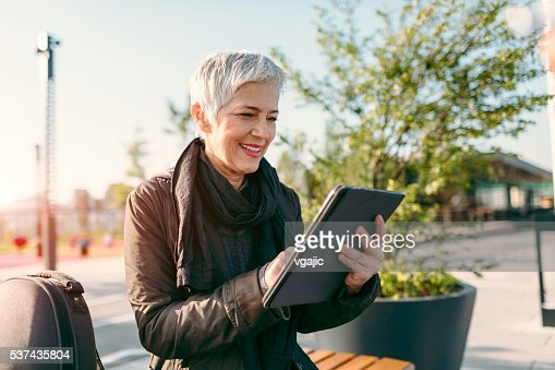 Mature Woman Sitting And Using Digital Tablet.