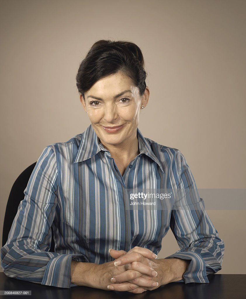 Mature woman sitting at desk with hands clasped, smiling, portrait