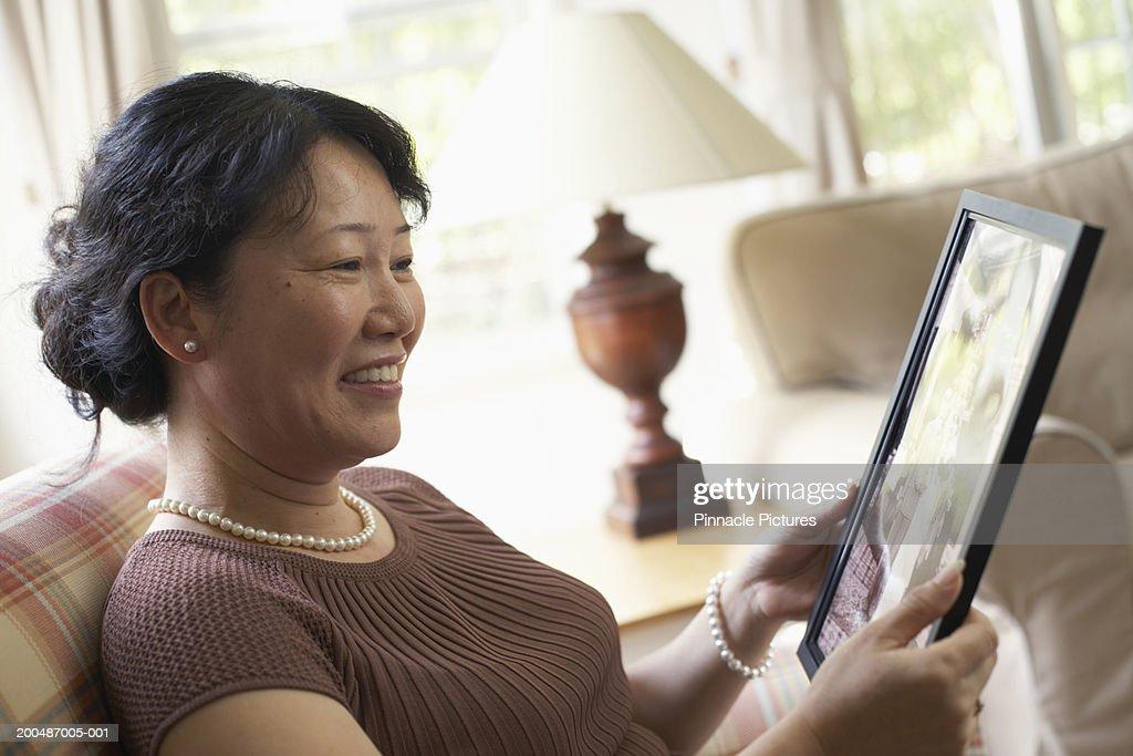Mature woman sitting at home, looking at photograph : Stock Photo