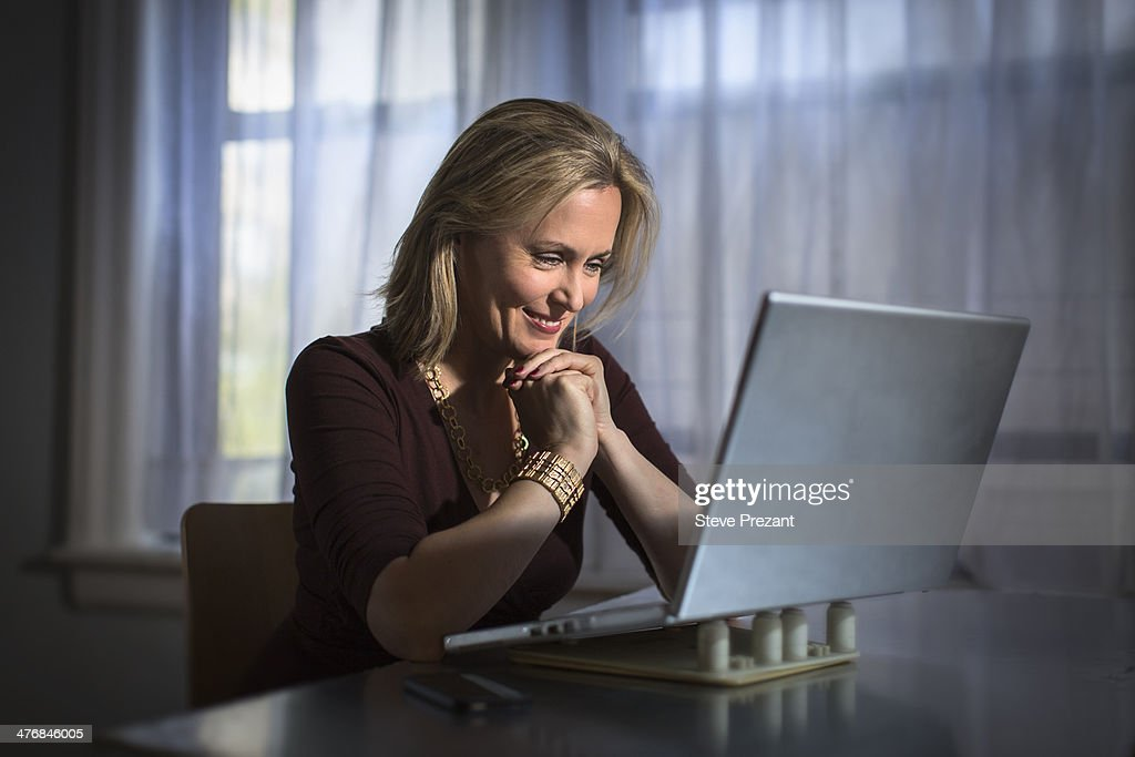 Mature woman sitting at home using laptop : Stock Photo