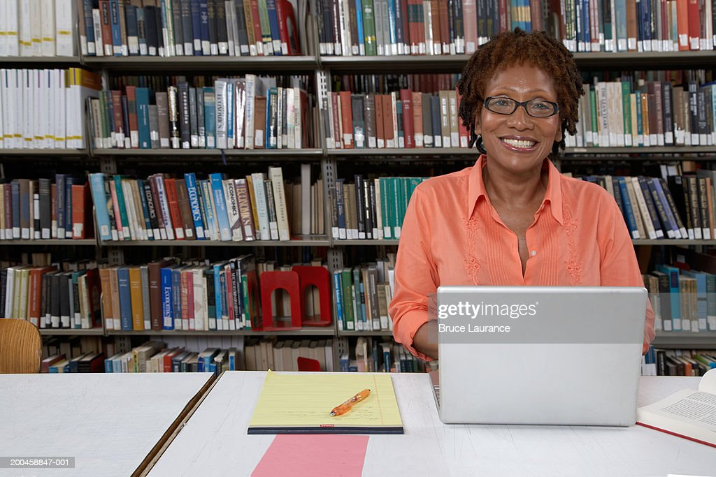Mature woman sitting at library table with laptop, smiling, portrait : Stock-Foto