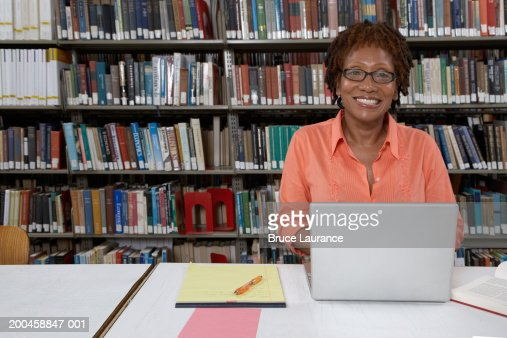 Mature woman sitting at library table with laptop, smiling, portrait : Photo