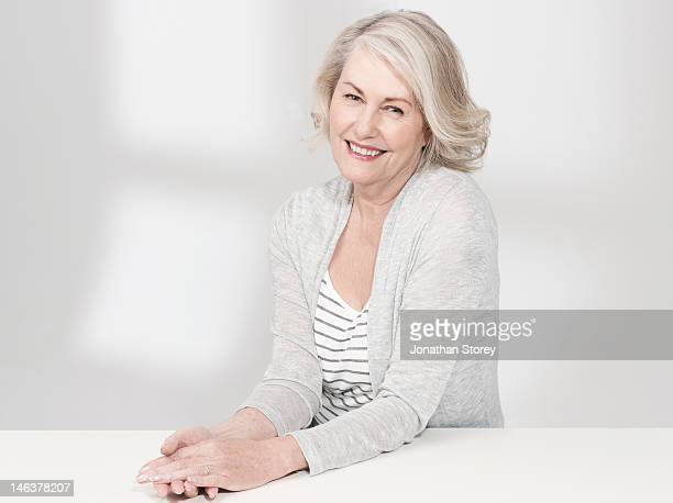 mature woman sitting at table holding her hands