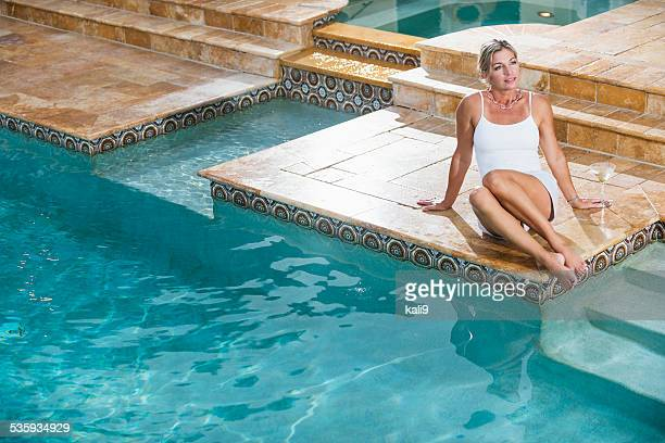 Mature woman sitting at the edge of a swimming pool