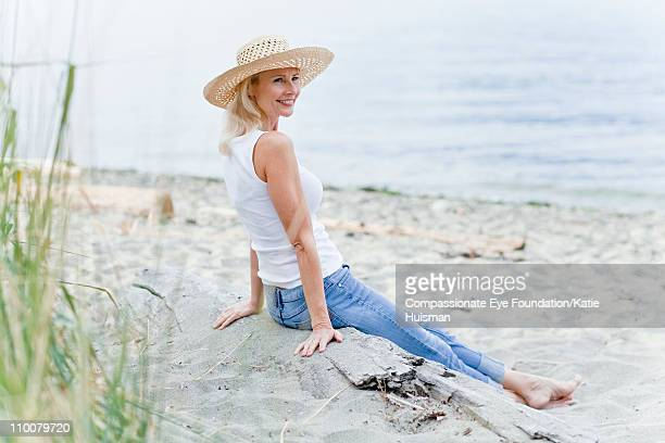 Mature woman sitting barefooted on the beach