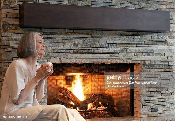 Mature woman sitting by fireplace, side view