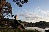 Mature woman sitting by lake