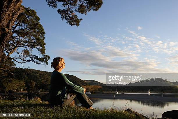 Mature woman sitting by lake