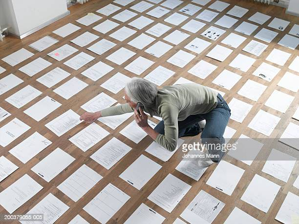 Mature woman sitting by papers laid out on floor, using telephone