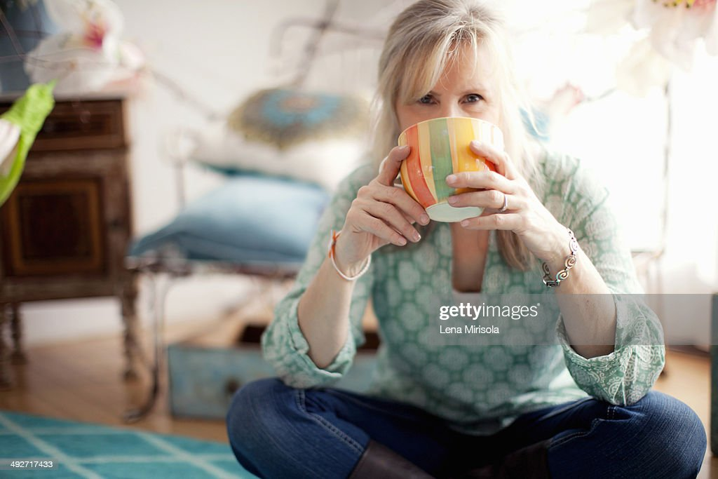 Mature woman sitting cross legged drinking coffee : Stock Photo