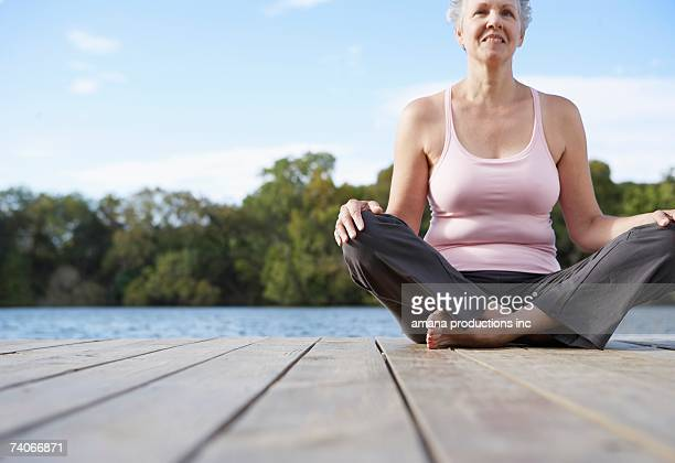 Mature woman sitting crossed legged by lake (low angle view)