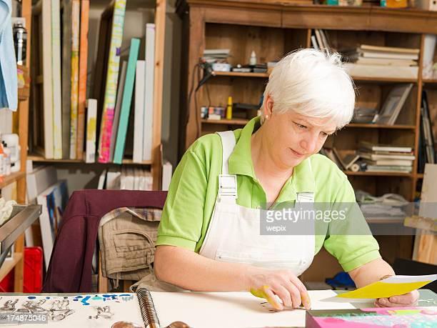Mature woman sitting desk artist sketching art studio