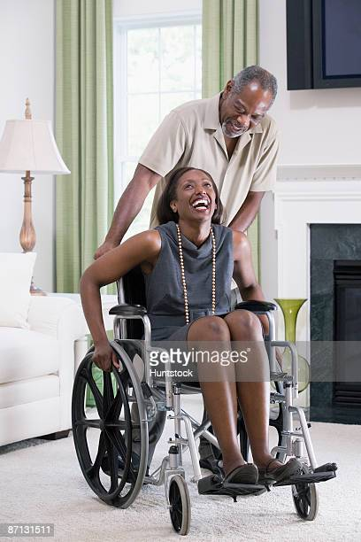 Mature woman sitting in a wheelchair with mature man standing behind her