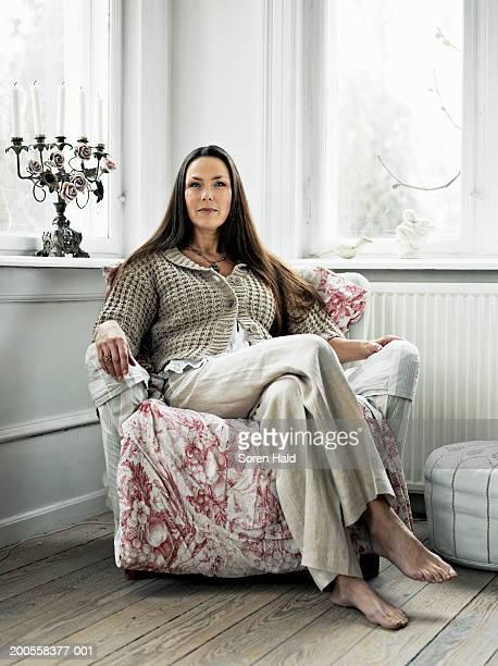 Mature woman sitting in armchair, portrait