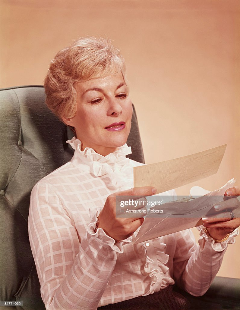 Mature woman sitting in chair, reading letter. (Photo by H. Armstrong Roberts/Retrofile/Getty Images) : Stock Photo
