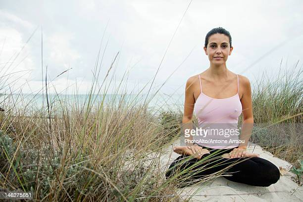 Mature woman sitting in lotus position on beach, portrait