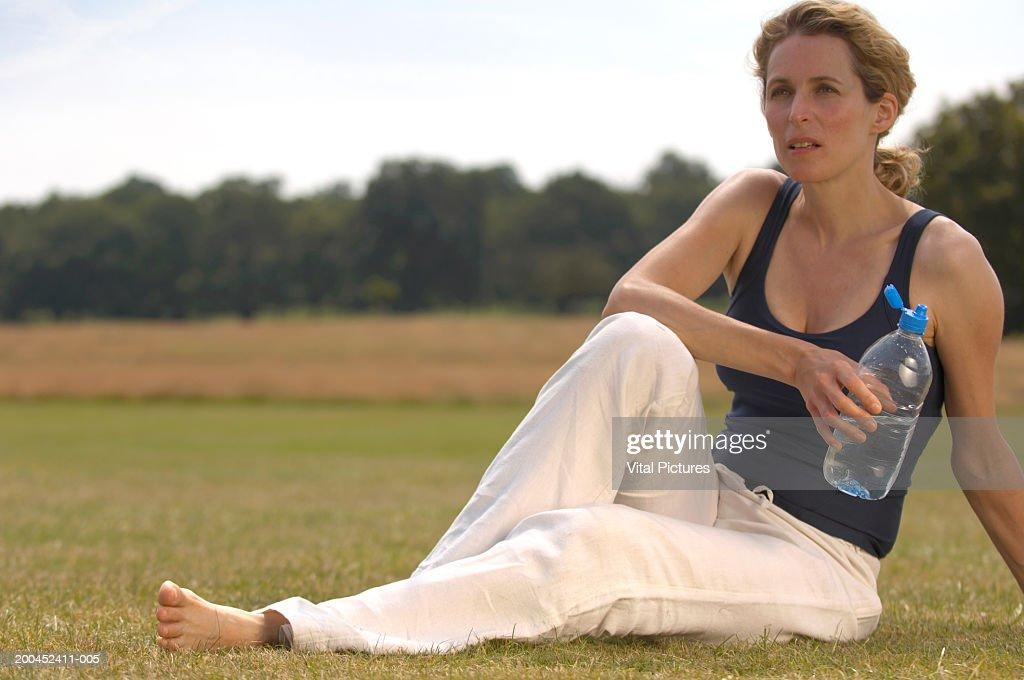 Mature woman sitting in park, holding water bottle : Stock Photo