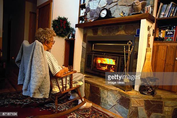 Mature woman sitting near fireplace