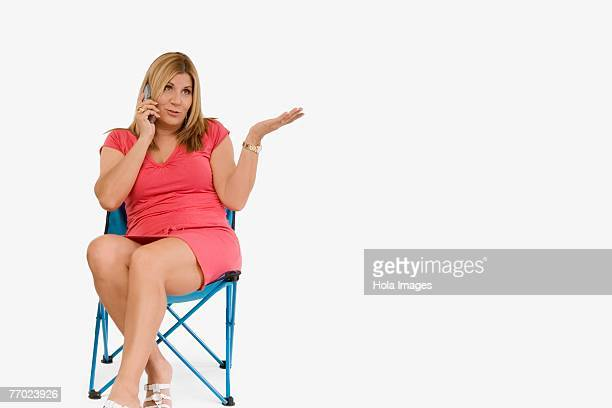 Mature woman sitting on a stool and talking on a mobile phone