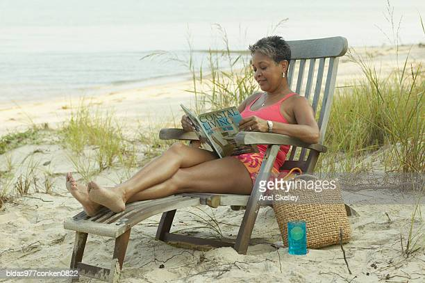 Mature woman sitting on an easy chair at the beach reading a book