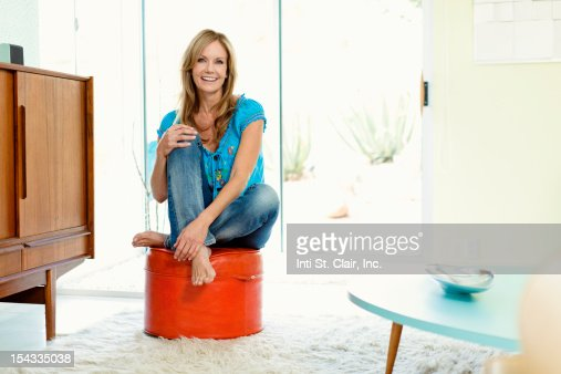 Mature woman sitting on an ottoman and smiling stock photo for Ottoman to sit on
