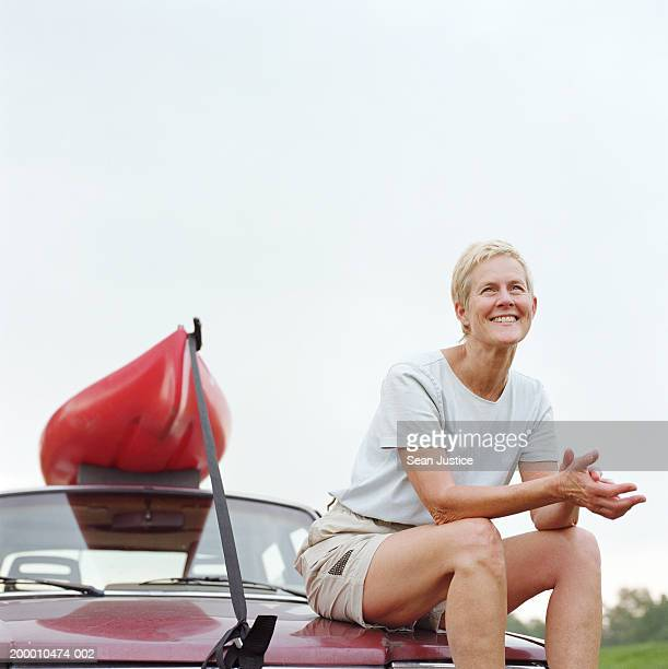 Mature woman sitting on car with kayak, portrait