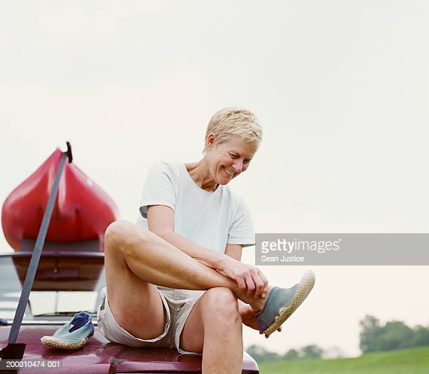 Mature woman sitting on car with kayak, putting on water shoes