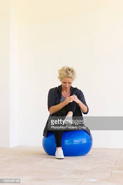 Mature woman sitting on fitness ball, hugging one knee