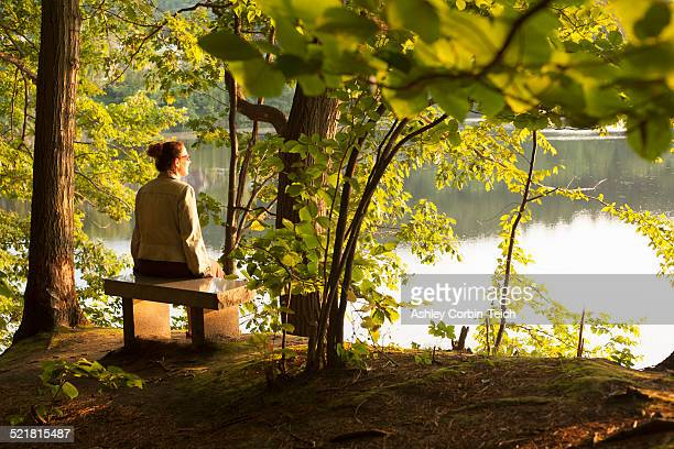 Mature woman sitting on lakeside seat in forest, Brattleboro, Vermont, USA