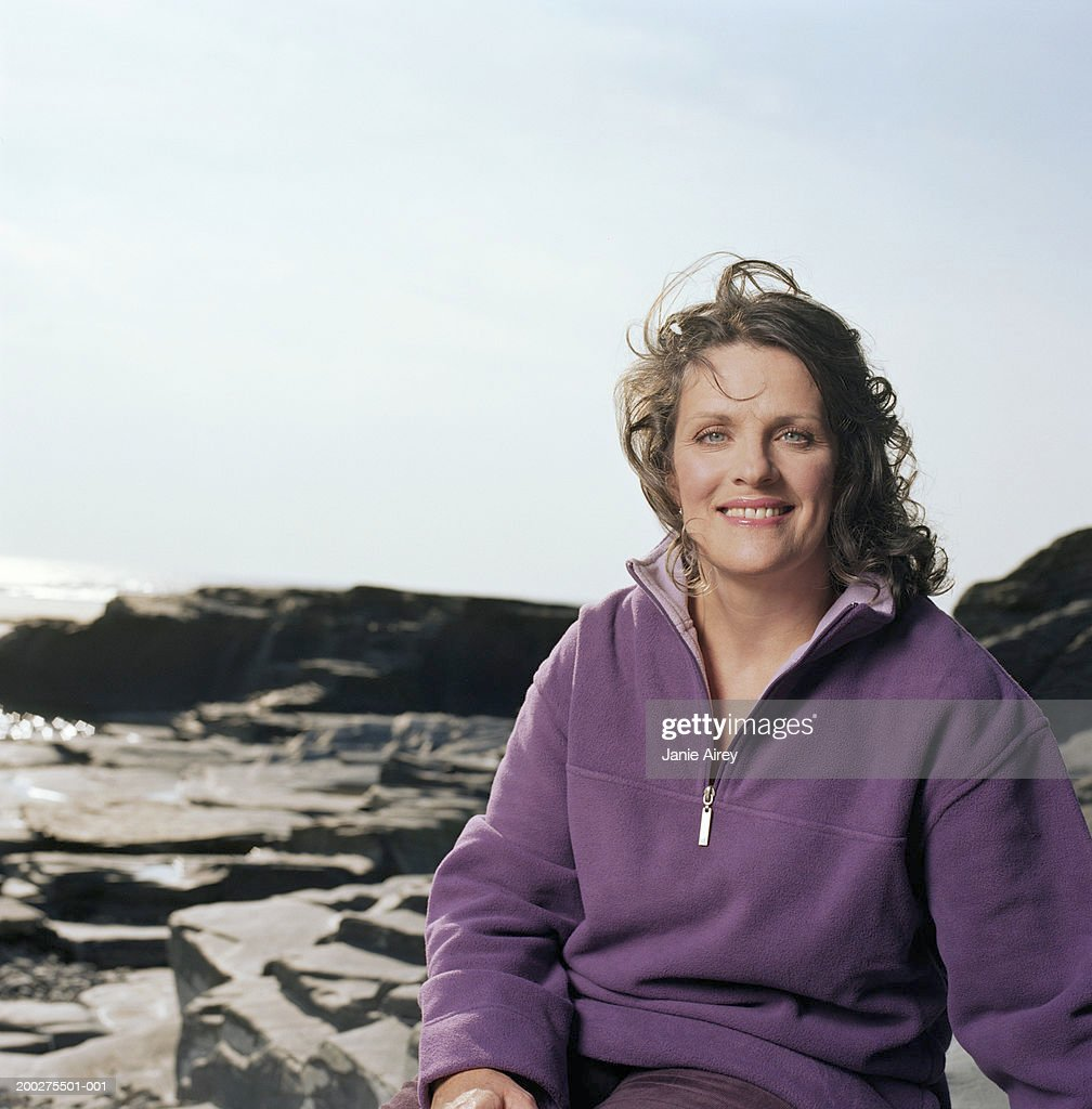 Mature woman sitting on rocks by sea, smiling, portrait