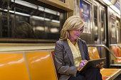 Mature woman sitting on subway train using digital tablet