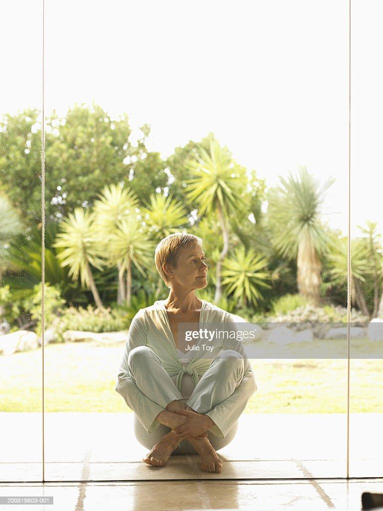 Mature woman sitting on tiled floor, garden in background : Stock Photo