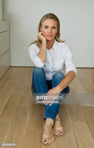 Mature woman sitting on wooden floor, portrait