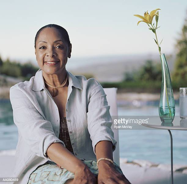 Mature woman sitting poolside, portrait