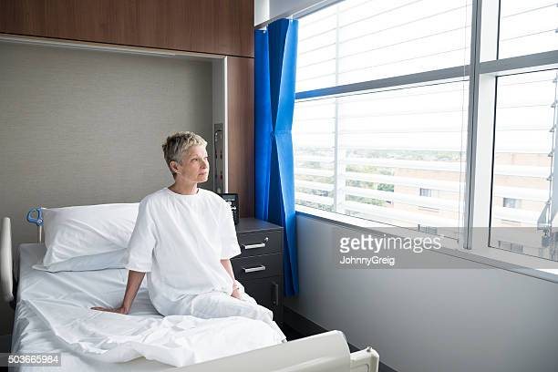 Mature woman sitting up in hospital bed looking through window