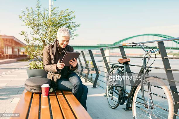 Mature Woman Sitting, Using Tablet And Drinking Coffee.