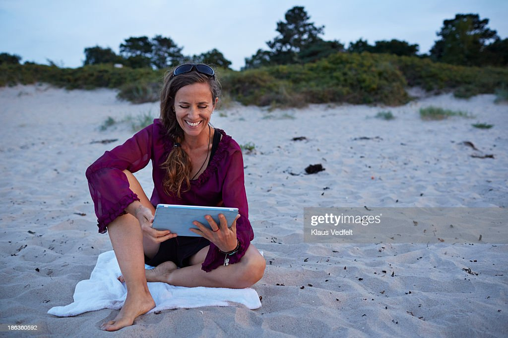 Mature woman sitting with tablet on the beach : Stock Photo
