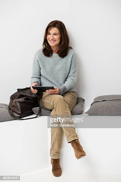 Mature woman smiling holding Ipad