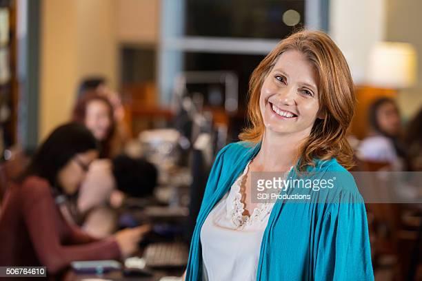 Reife Frau lächeln im college-Bibliothek computer lab