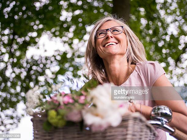 Mature woman smiling while cycling under trees