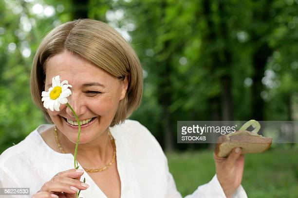 Mature woman smiling, while holding a flower and a sandwich