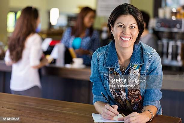 Mature woman smiling while journaling in coffee shop