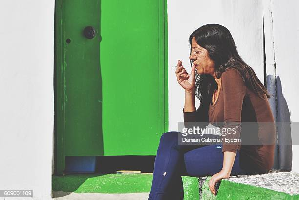 Mature Woman Smoking Cigarette While Sitting On Retaining Wall