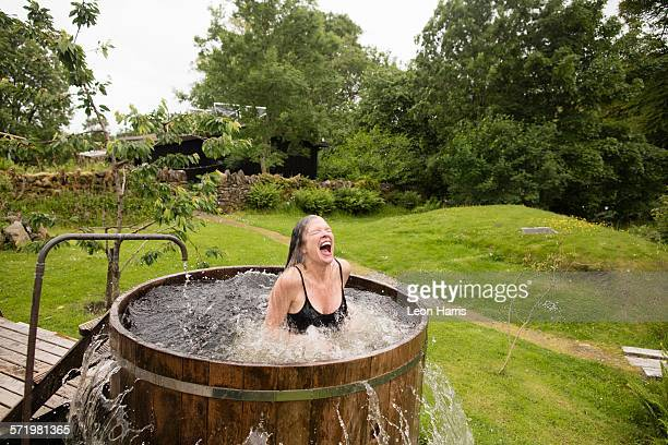 Mature woman splashing in fresh cold water tub at eco retreat