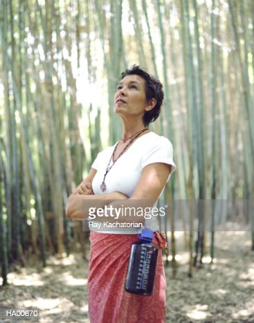 Mature woman standing amongst bamboo trees