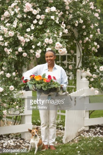 Mature woman standing beneath archway in garden, smiling, portrait : Stock Photo