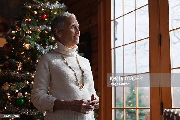 Donna matura in piedi con albero di Natale, guardando attraverso la finestra